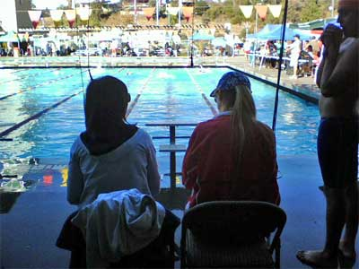 Two swim team moms timing during a meet at the pool